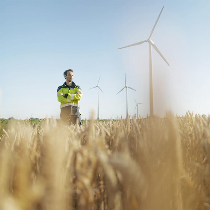 Employees in the field in front of wind turbines.
