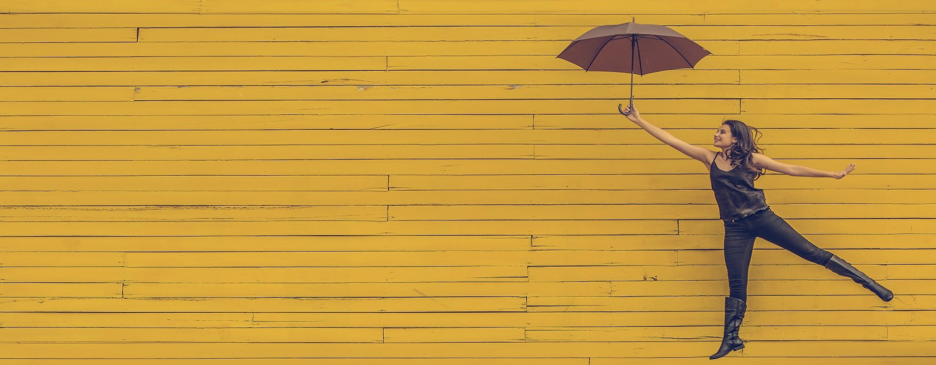 female holding an umbrella against a yellow wall 1920 x 750