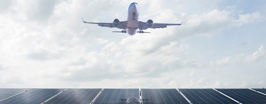 Airplane in flight and view of solar panels in the background | WSP