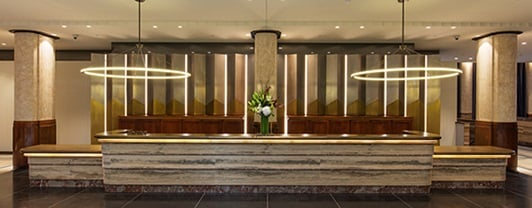 Lighting has been used to showcase the art deco features and create a warm atmosphere within this art deco hotel.