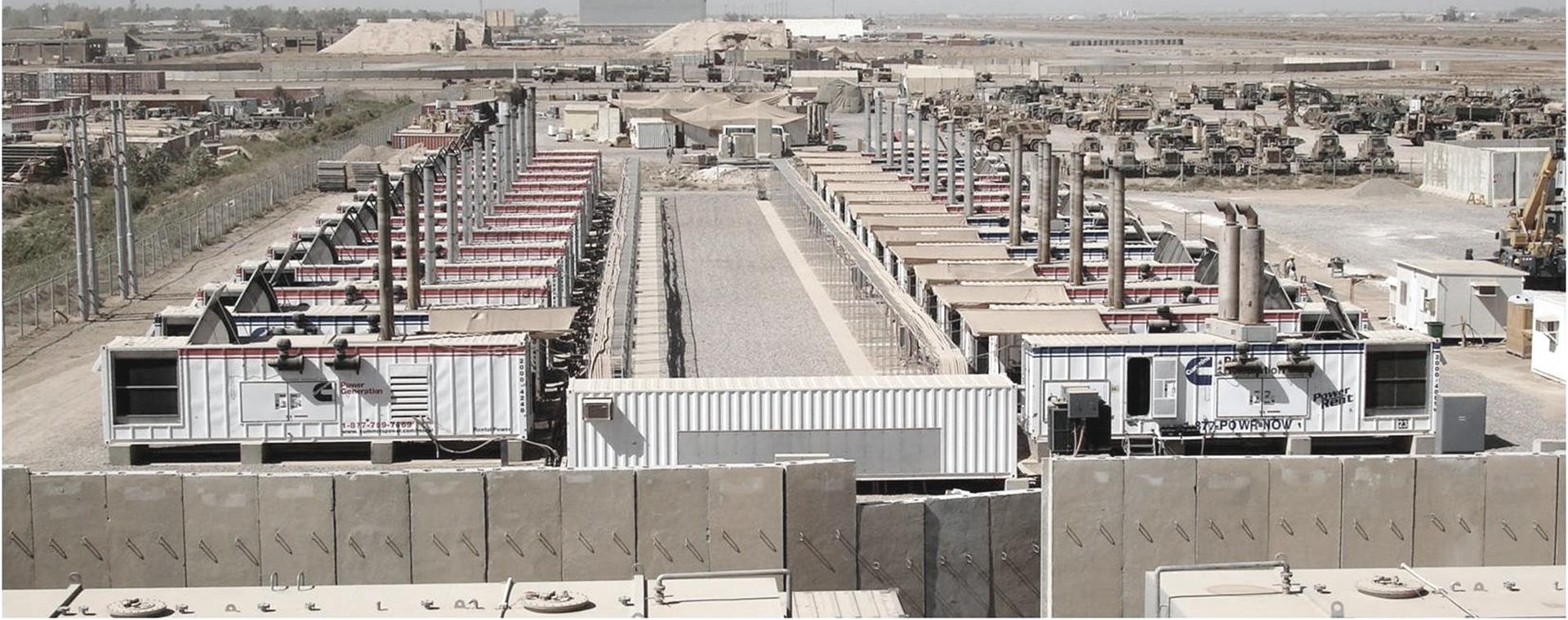 Exterior view of row of diesel generators behind a cement barricade