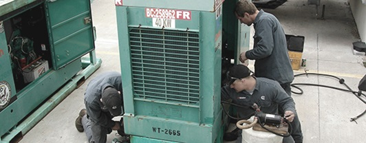 group of mechanics performing routine maintenance on a generator