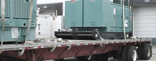 Generator on a flatbed trailer, waiting for deployment from a FEMA distribution center