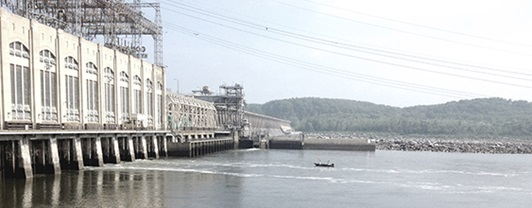 Wide view  across body of water with hydroelectric dam on the left