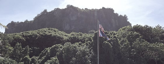 View of Guam mountain top with high cliffs, blue sky, and flags in the foreground