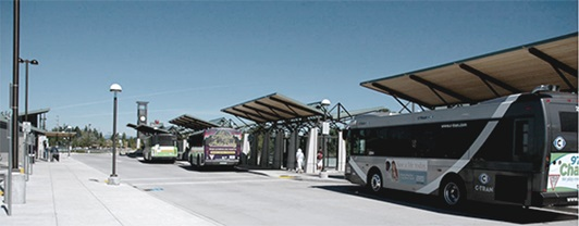 Outdoor view of bus transit center where several buses are parked under curbside canopies