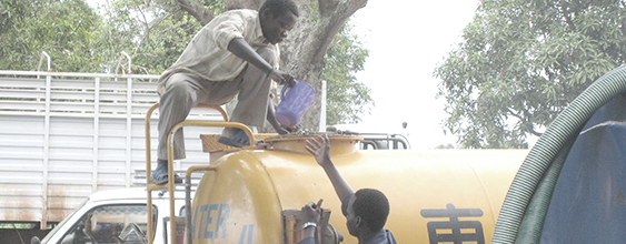 Two men supply fresh water from a tanker truck in South Sudan, where WSP implemented a clean water program