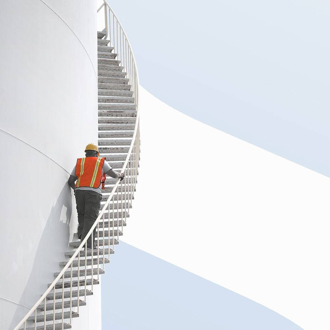 Our History image, hard hat worker climbing stairs that curve around a white tower